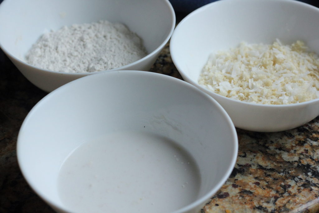 3 bowl used to make coconut shrimp. One with coconut milk, an other with flour and lastly panko and coconut flakes.