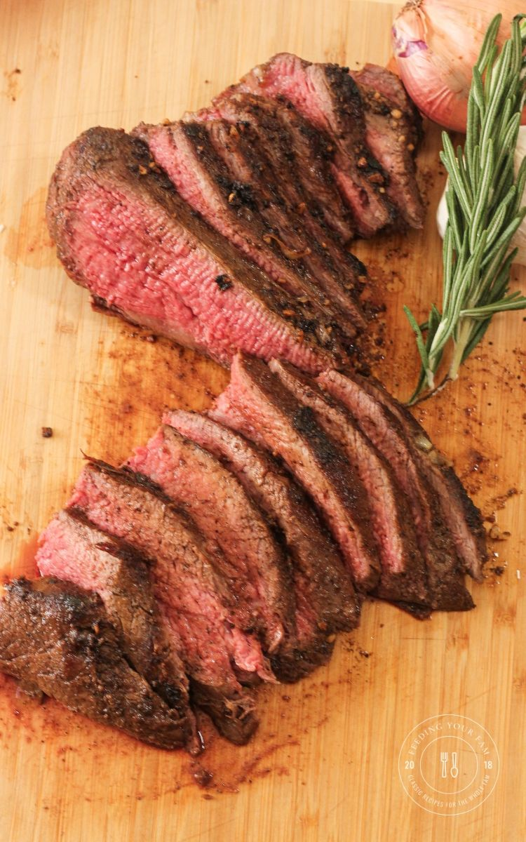 sliced tri tip on a wooden cutting board
