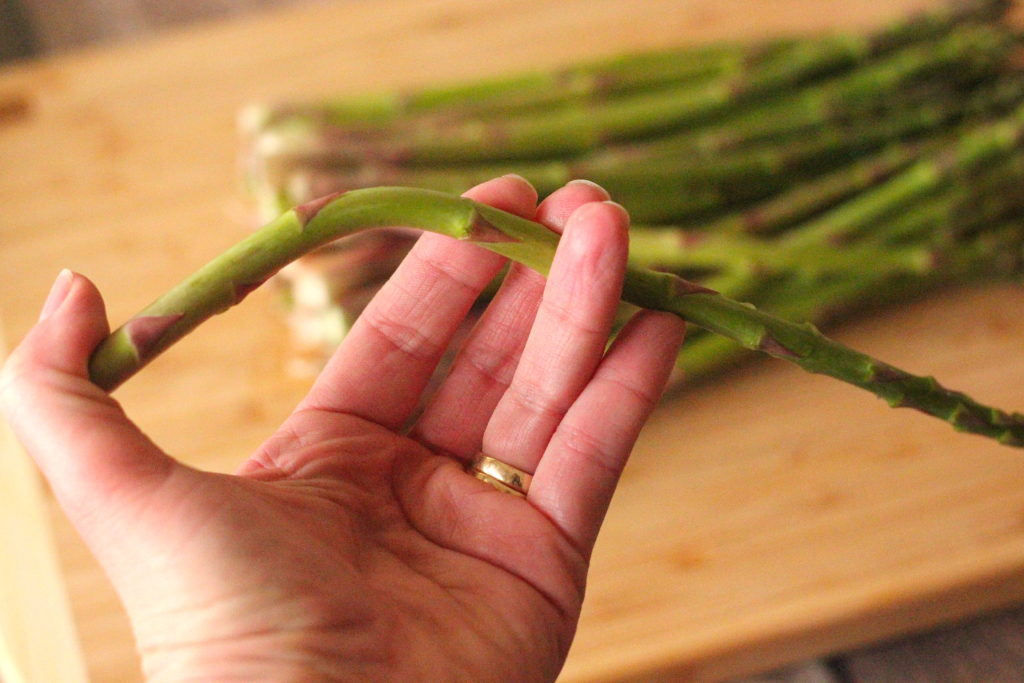bending a sprig of asparagus in one hand to see where to cut