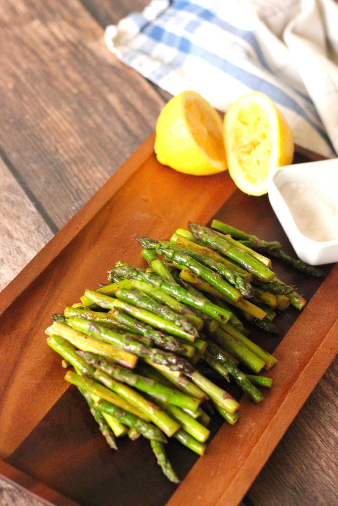 Sauteed asparagus on a wooden board with lemons