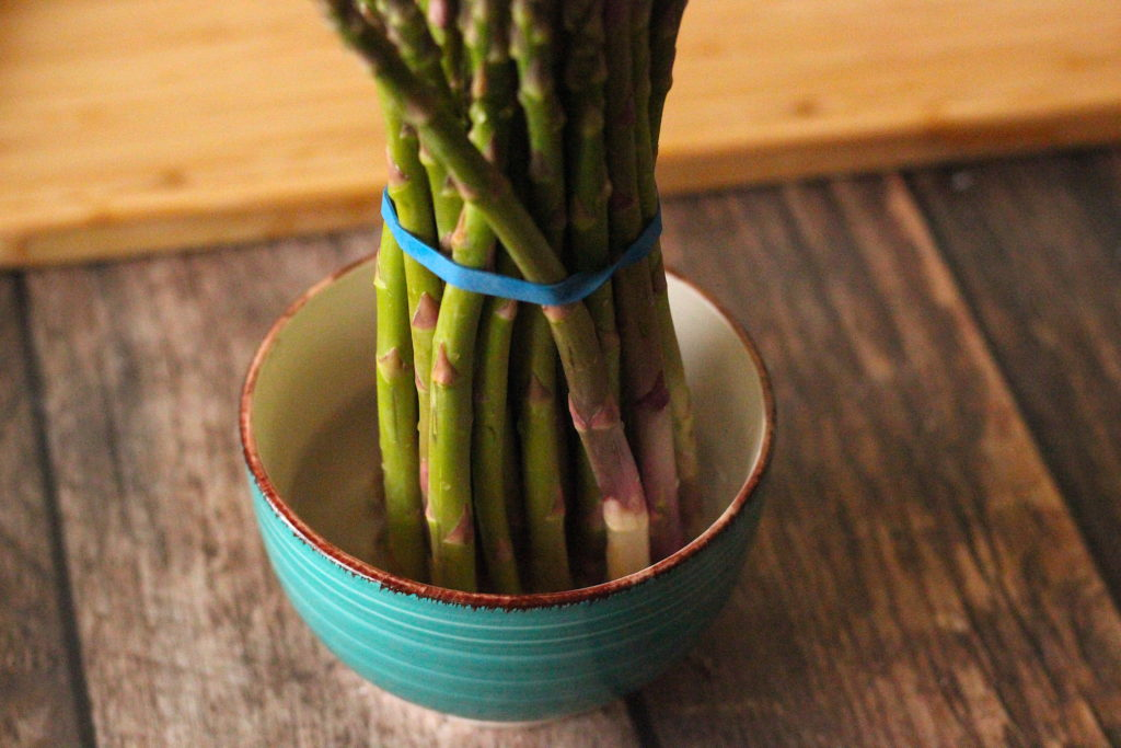 Bunch of asparagus standing in a small bowl of water