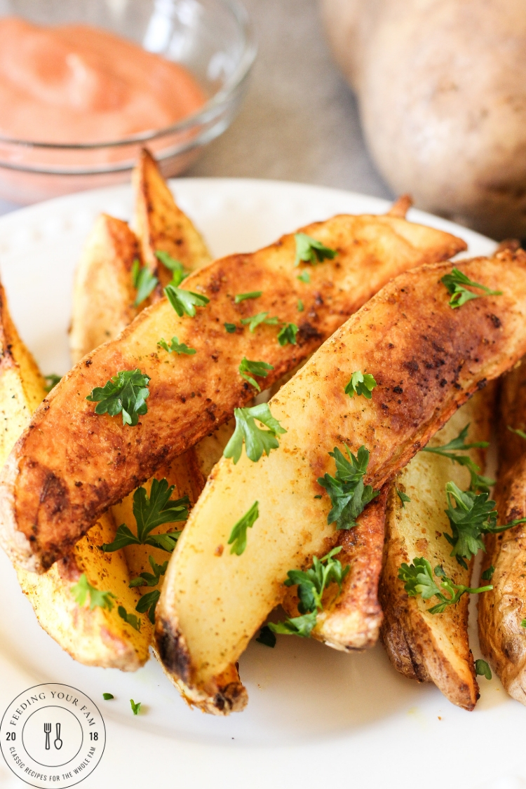 golden potato wedges on a plate topped with parsley