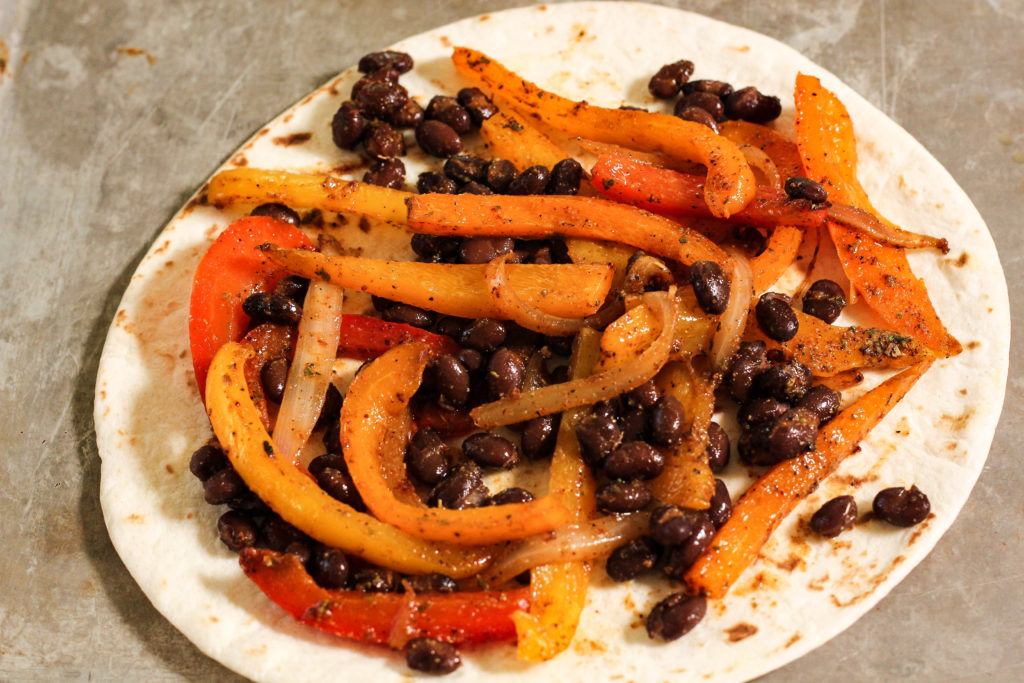 peppers and black beans on a tortilla to make quesadillas