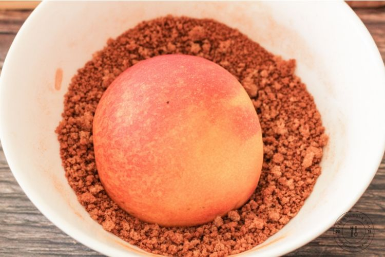 slice peach cut side down in a bowl of brown sugar and cinnamon