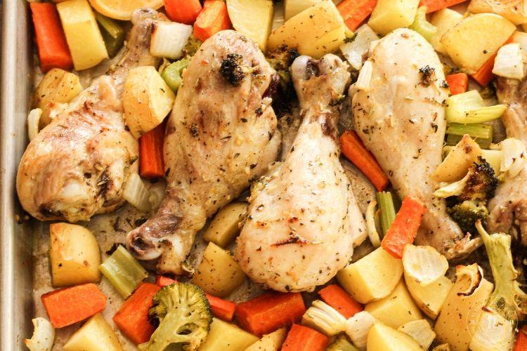 lemon chicken drumsticks with veggies on a sheet pan