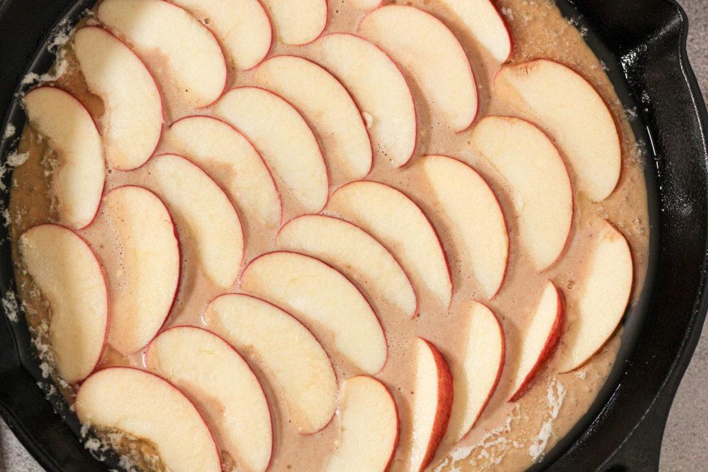 german apple pancake batter in a cast iron skillet