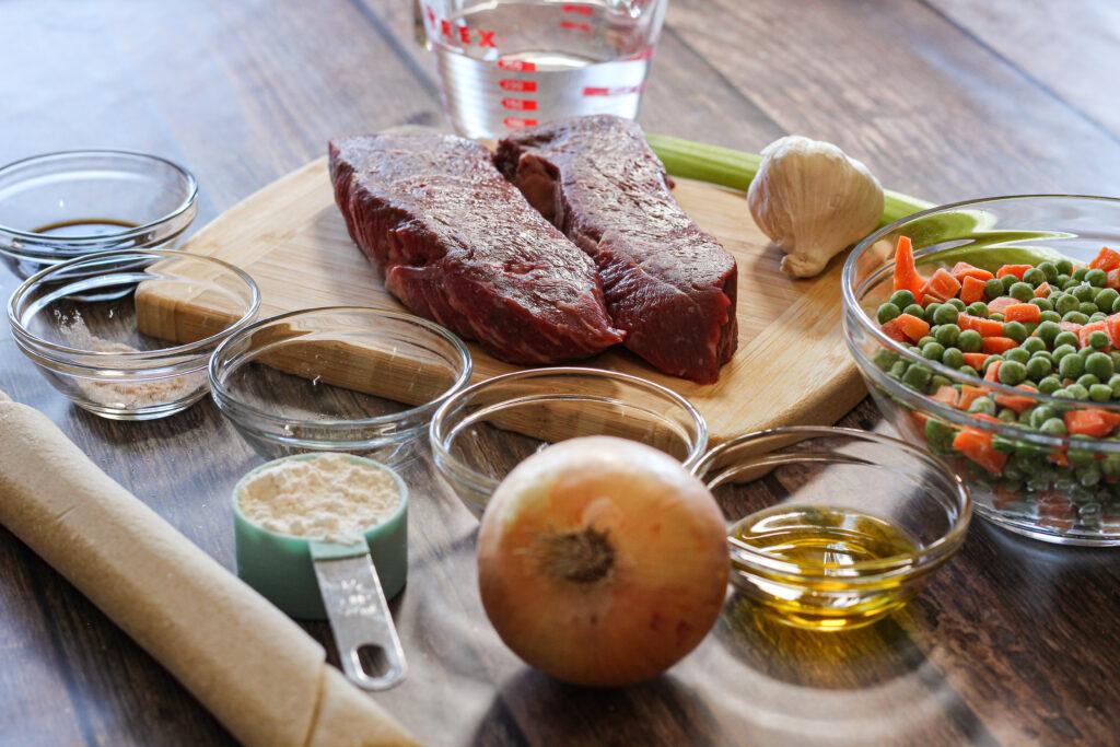 ingredients for beef pot pie. pie crust, steak. onion, garlic, vegetables and spices