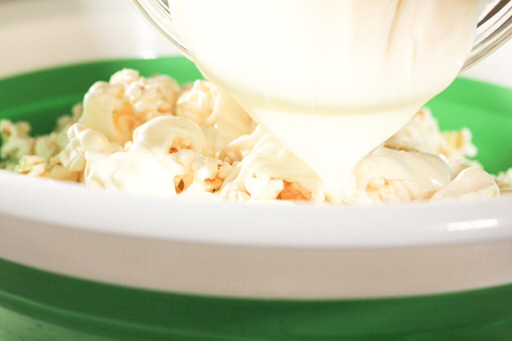 pouring white chocolate on popcorn