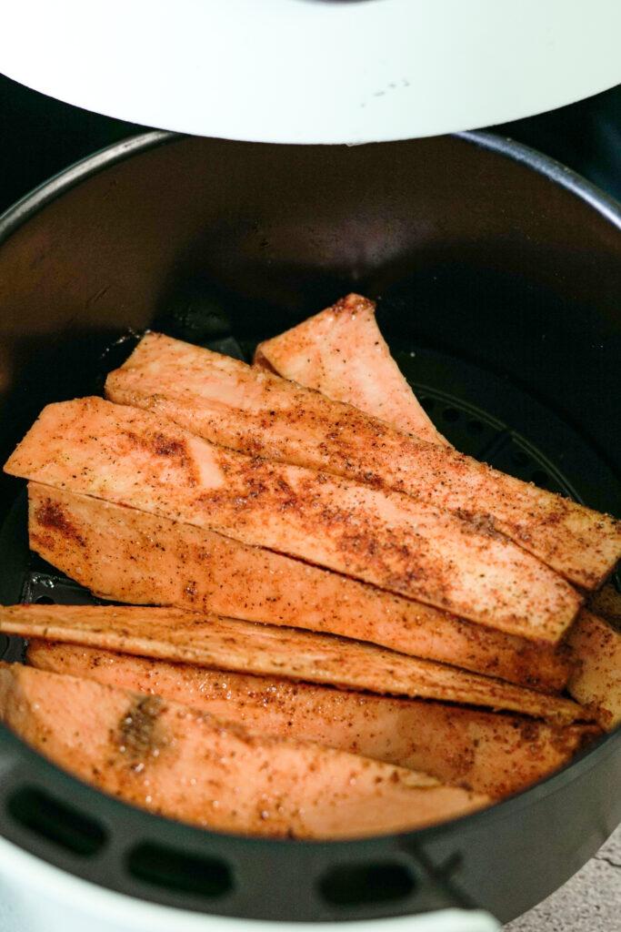seasoned sweet potatoes in air fryer basket