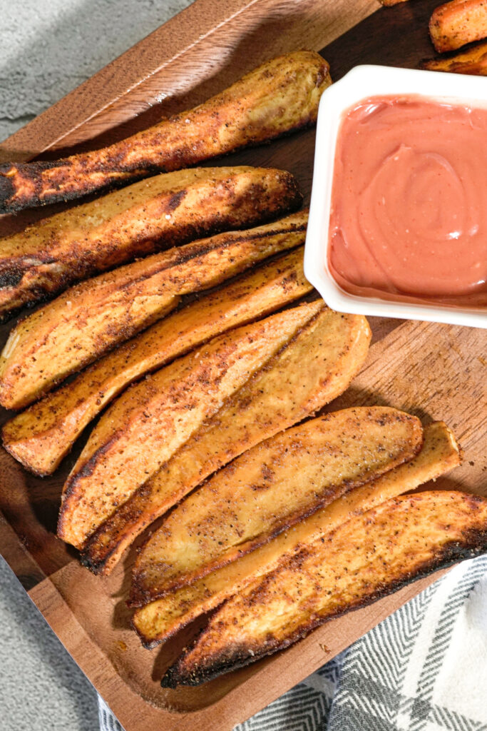 crispy air fried sweet potatoes on a wooden serving platter with dipping sauce