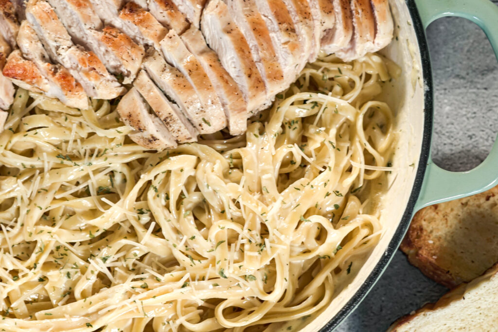 pan of asiago cheese alfredo with sliced chicken