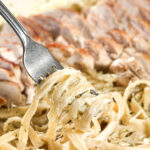 fork lifting asiago alfredo out of a pan