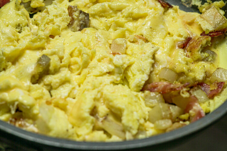scrambled eggs and bacon in a skillet