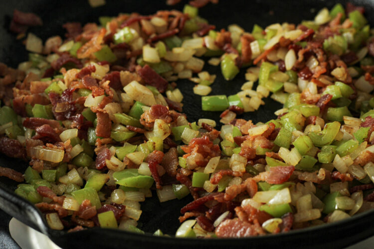 cooked bacon, onion and green pepper in a cast iron pan