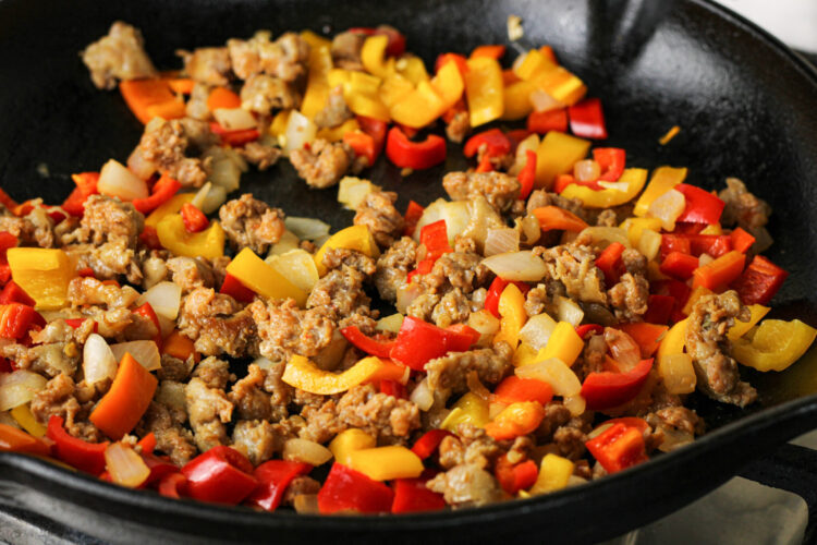 browned sausage, peppers and onions in a black cast iron pan