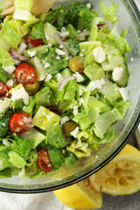 green salad with tomatoes, feta cheese, red onions, cucumbers and green onions
