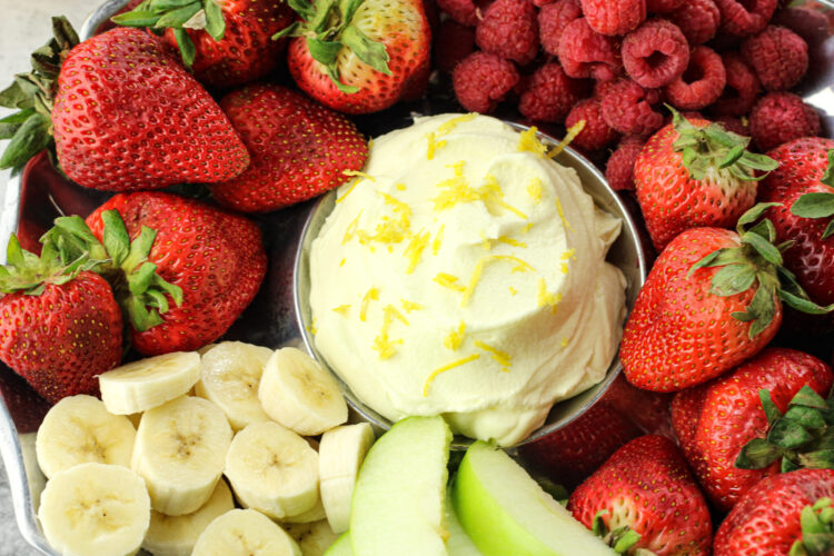 bananas, strawberries, raspberries and green apples surrounding yellow lemon fruit dip in the center