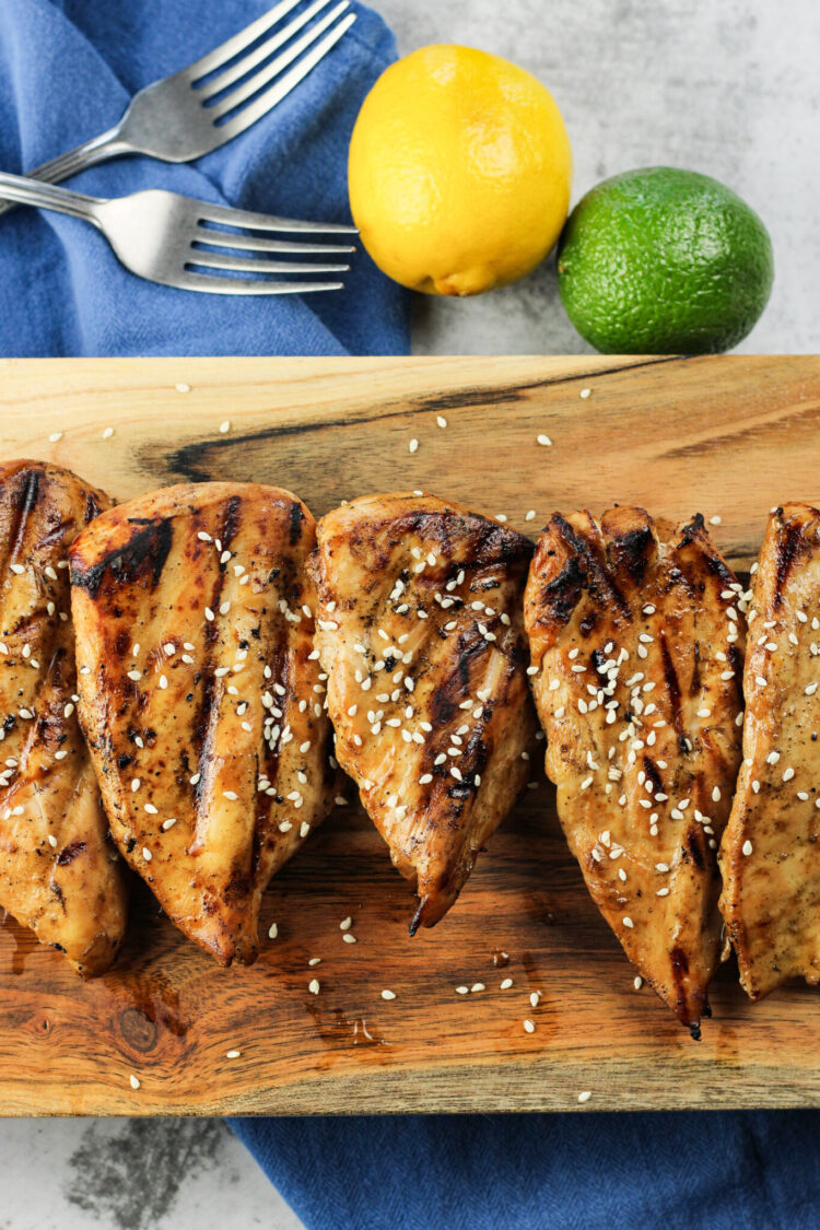 grilled teriyaki chicken breasts on a wooden board with forks and a lemon and lime on the side