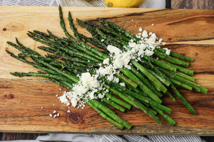 cooked asparagus on a wooden platter with feta cheese