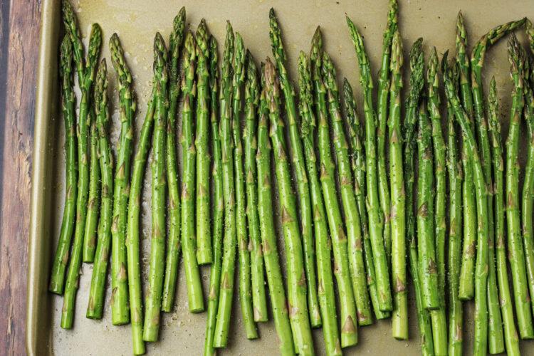 asparagus spears seasoned on a baking sheet
