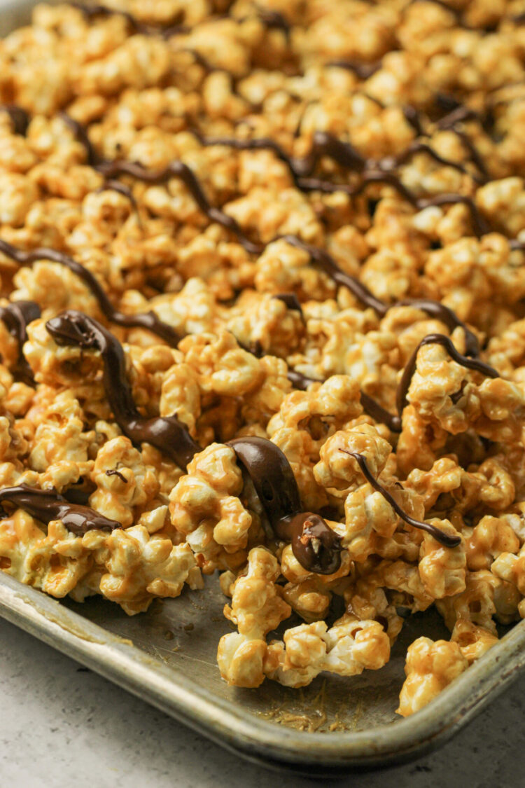 peanut butter covered popcorn with chocolate drizzle