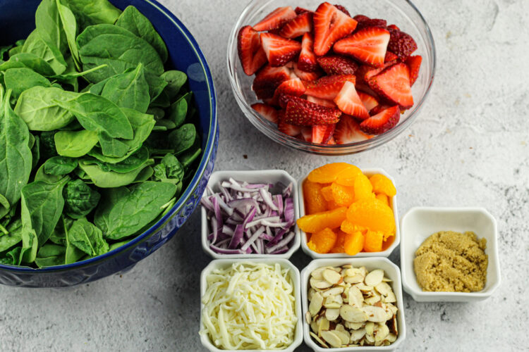 big bowl of spinach, bowl of sliced strawberries, mandarin oranges, sliced red onions, mozzarella cheese, almonds and brown sugar