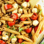 penne pasta with mozzarella pearls, tomatoes and basil in a balsamic dressing