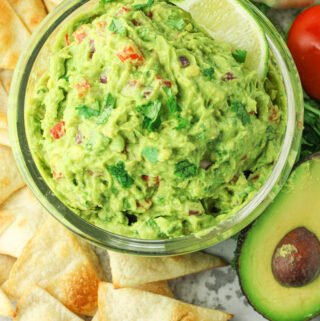 guacamole surrounded by chips and avocado