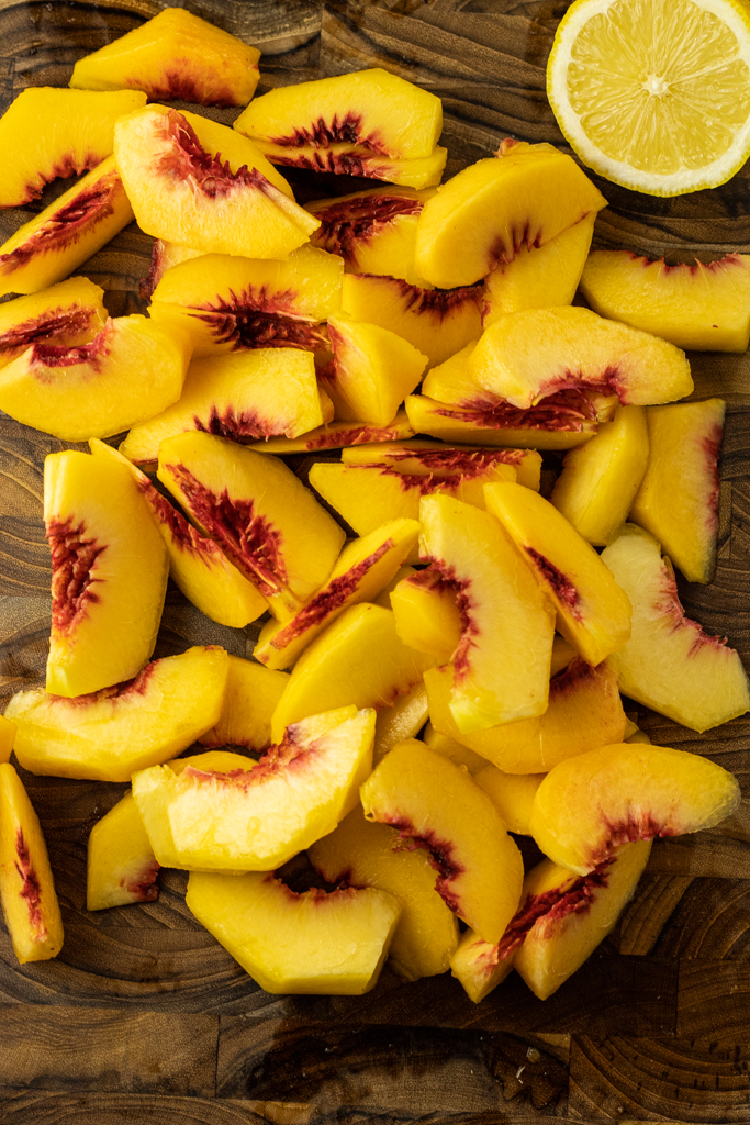 sliced peaches on a wooden cutting board with a half a lemon