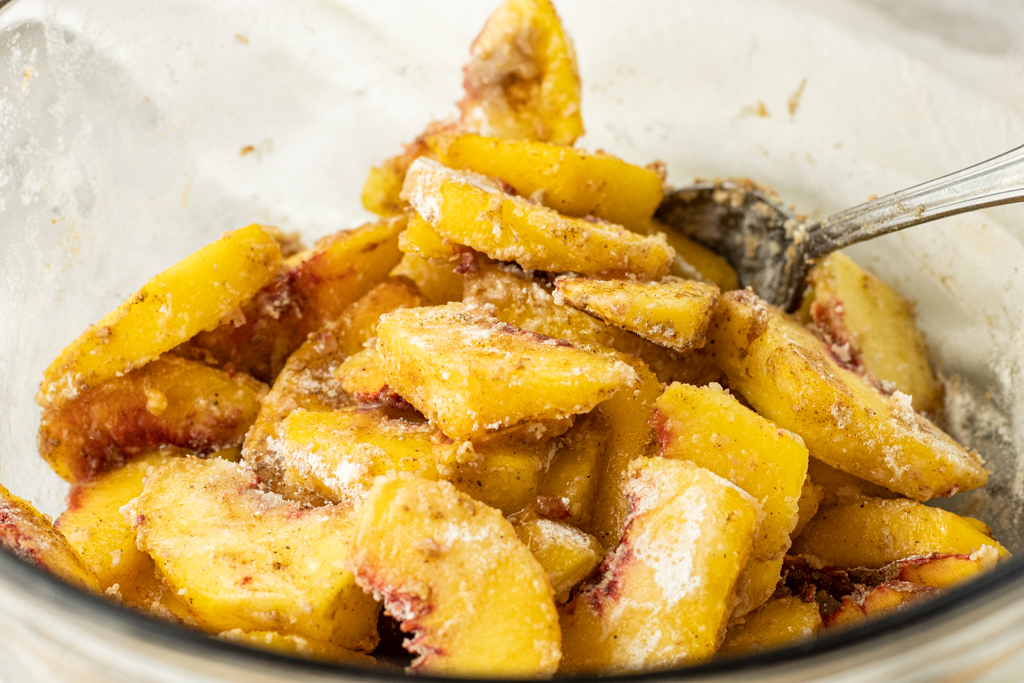 peaches covered in flour, sugar and spices in a mixing bowl