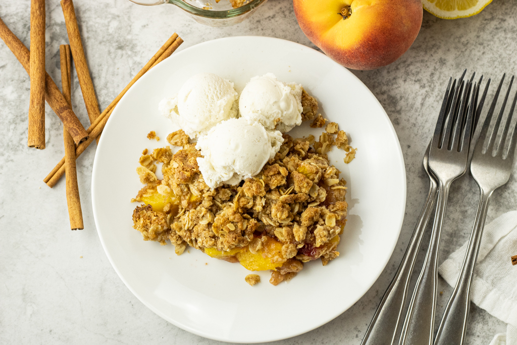 white plate with peach crisp and vanilla ice cream on a white plate