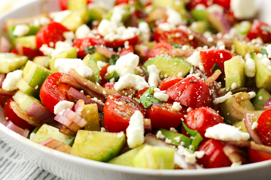 tomato cucumber feta salad in a white bowl