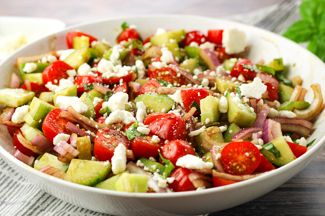 tomato cucumber salad in a white bowl