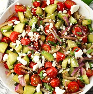 cucumber tomato red onion salad with feta cheese in a white bowl