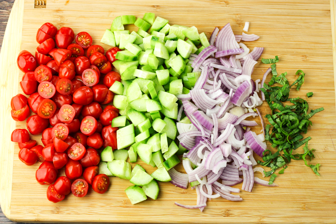 sliced tomatoes, cucumbers, red onions and basil on a wooden cutting board