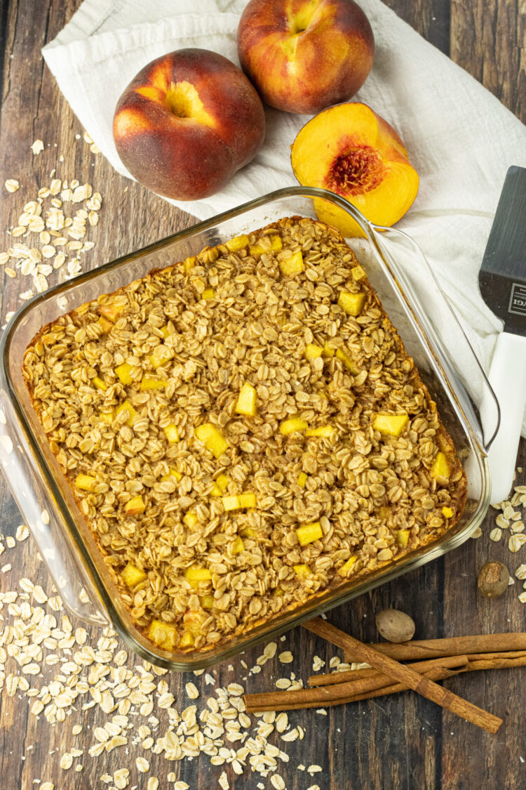 pan of baked oatmeal surrounded by dry oatmeal, peaches and cinnamon sticks