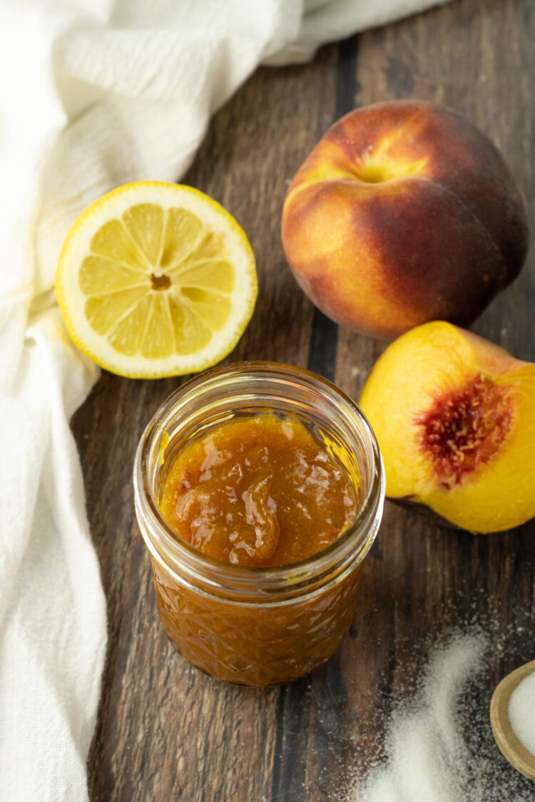 peach jam in a glass jar surrounded by peaches and a sliced lemon