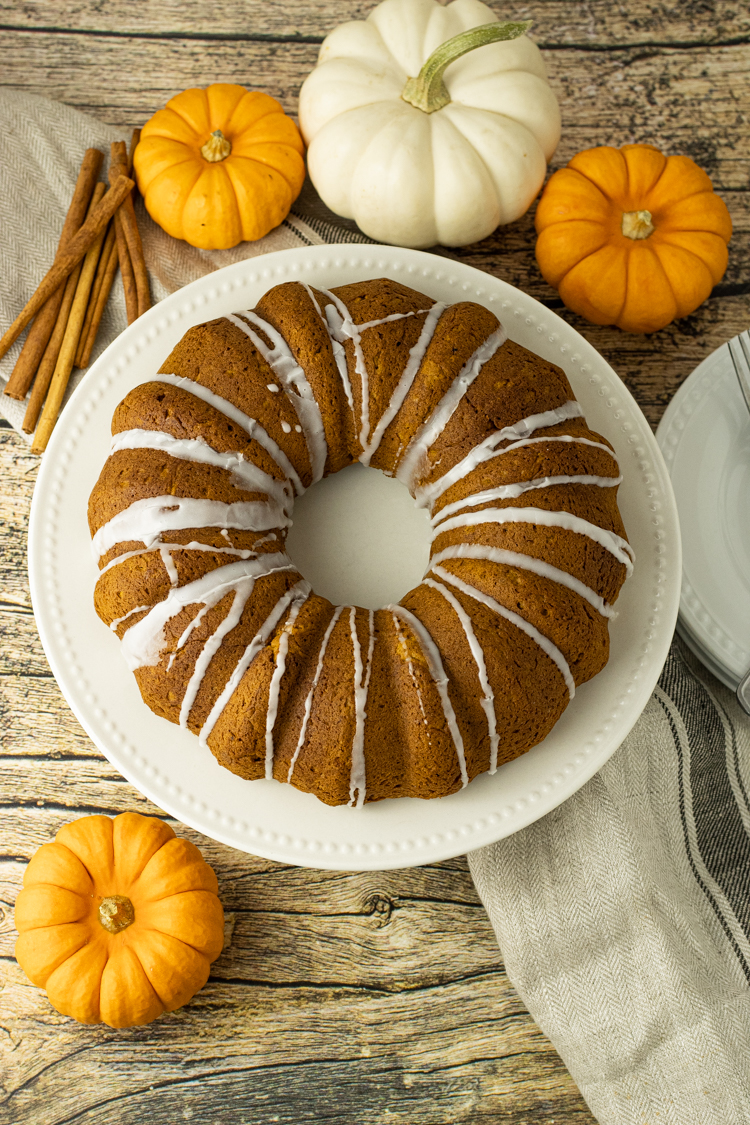 pumpkin bundt cake surrounded by small pumpkins