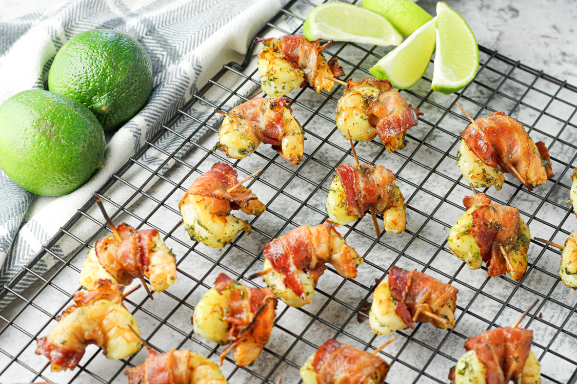 shrimp wrapped in bacon, seasoned with lime on a cooling rack