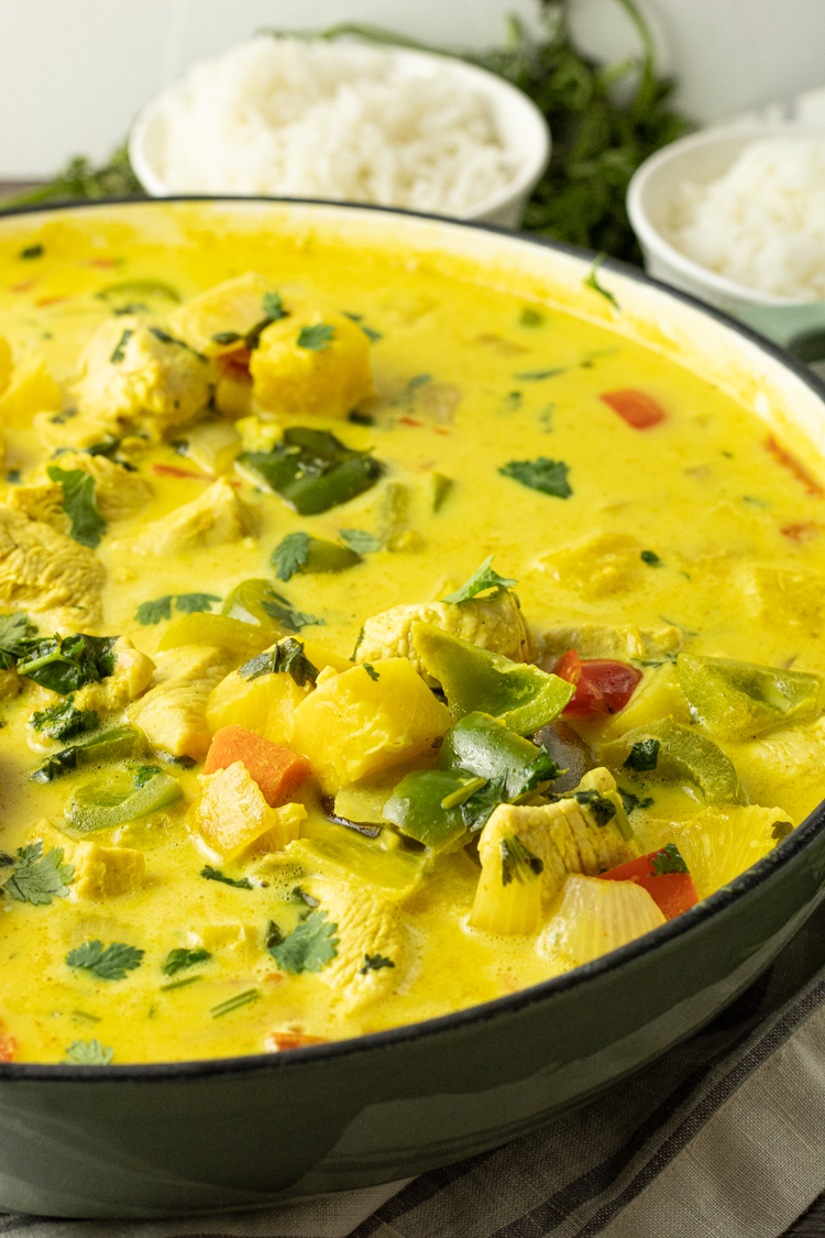 big pan of pineapple curry with green peppers, onions, chicken, red peppers and pineapple in a yellow curry sauce