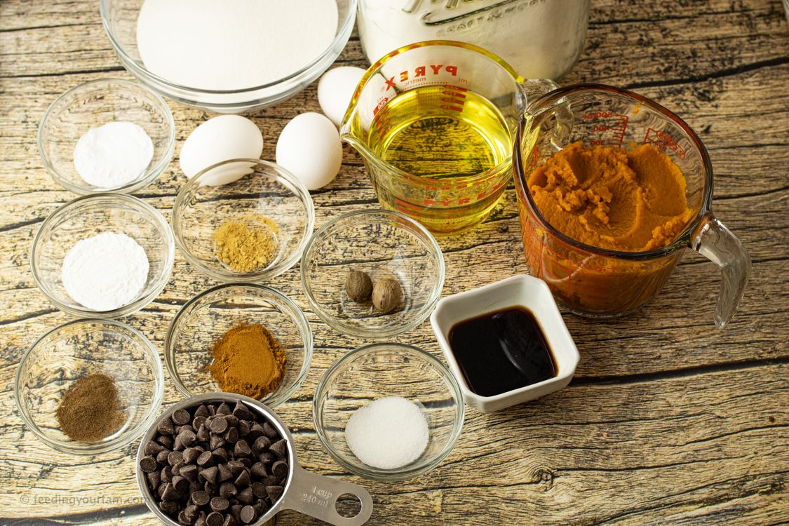 Ingredients for pumpkin bread in bowls and measuring cups