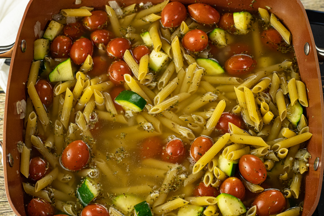one pan pasta dish with tomatoes, zucchini and chicken broth