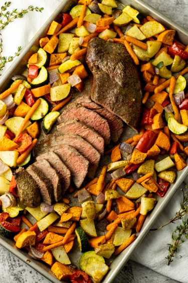 sliced steak surrounded by roasted vegetables on a sheet pan