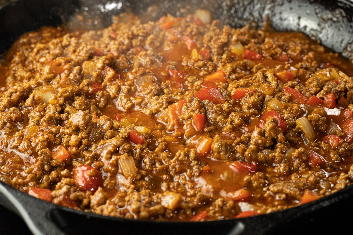 simmering pan of ground beef, onions, peppers and tomato sauce