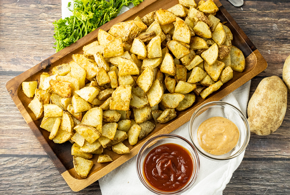 potato triangle pieces on a wooden platter with ketchup and dipping sauce