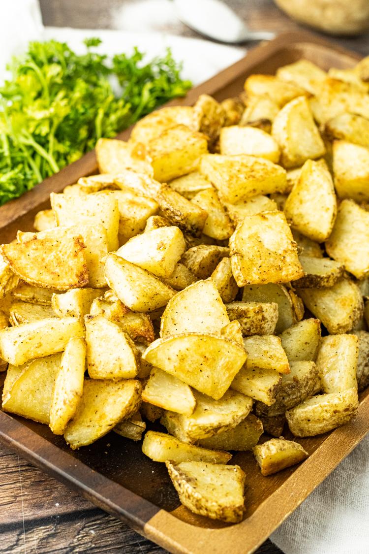crispy potato slices on a wooden platter