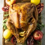 baked turkey surrounded by lemons, pomegranates, spices and apples