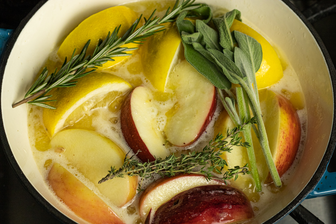 pan of butter, apples, lemons, rosemary, sage and thyme