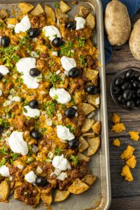 baking sheet of potato pieces topped with chili, sour cream and olives