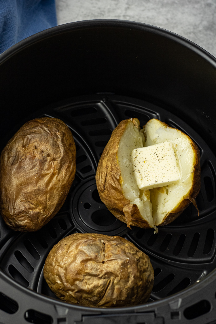 three baked potatoes in an air fryer basket, one sliced in half with butter